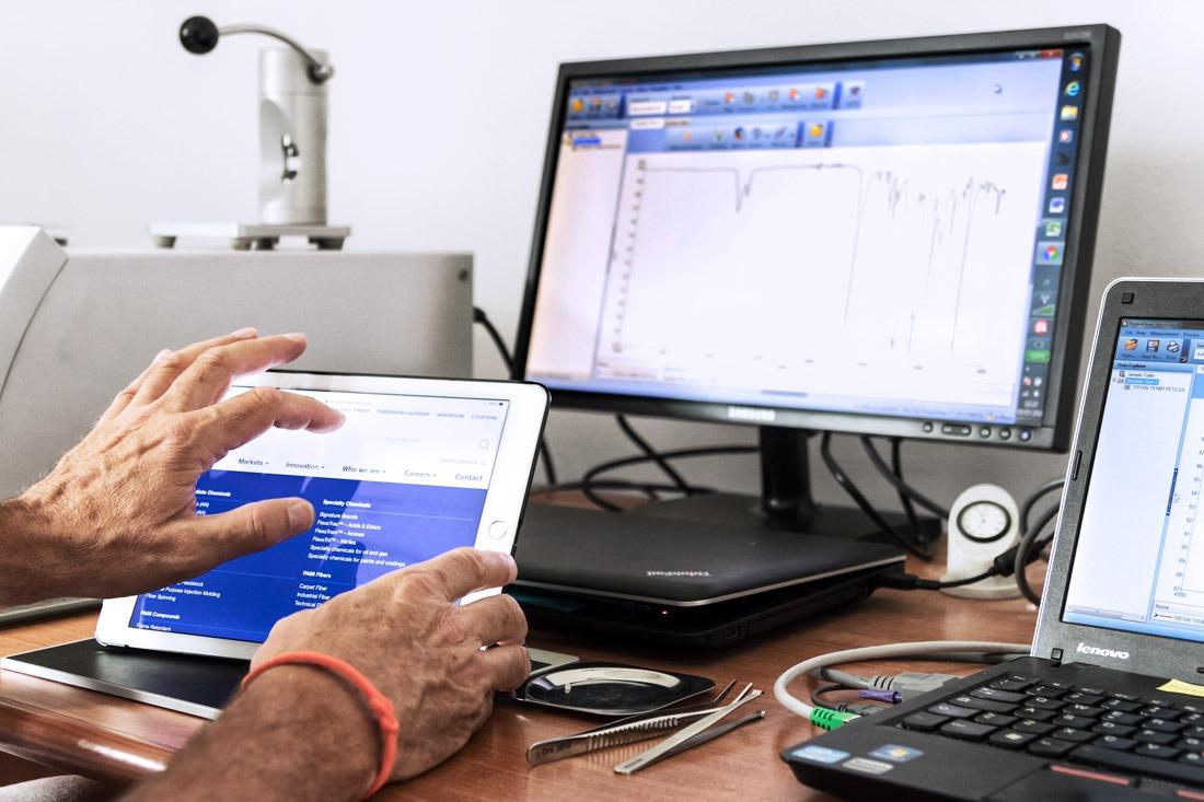 Tecnico di laboratorio che svolge alcuni test con un tablet ed un computer